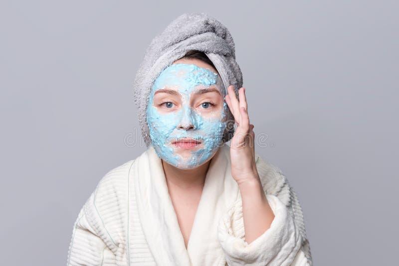 Kvinna som applicerar den ansikts- leramaskeringen på brunnsortsalongen eller hemma, skincaretema Framsidamaskering, brunnsortskö arkivbild