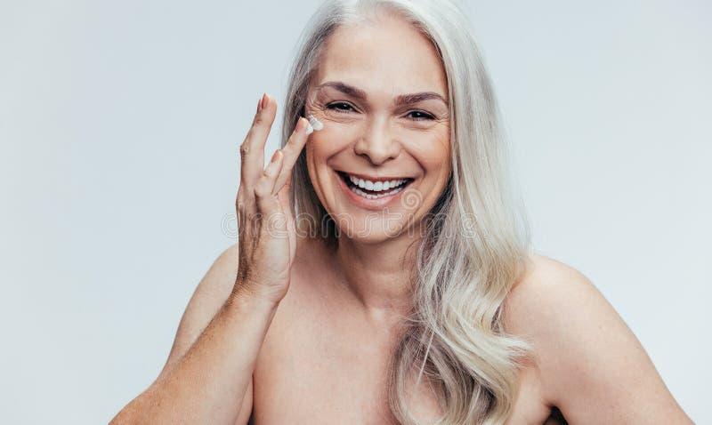 Kvinna som applicerar den anti-åldras skönhetsmedlet arkivfoto