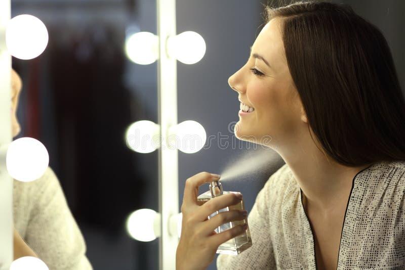 Kvinna som applicerar doft med en sprej arkivbild