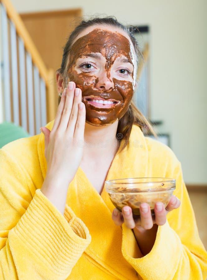 Kvinna som applicerar en ansikts- maskering royaltyfria bilder