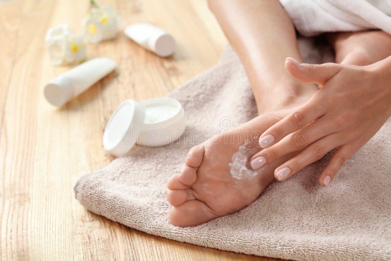 Kvinna som applicerar fotkräm på handduken, closeup royaltyfria bilder