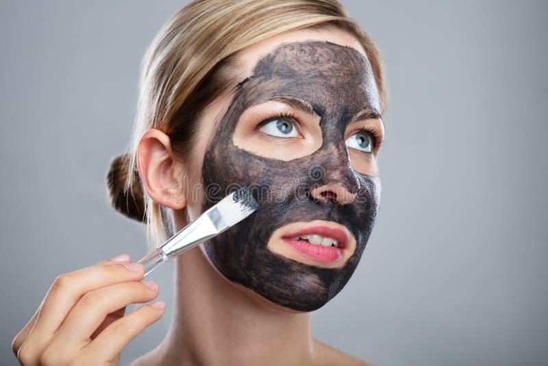 Kvinna som applicerar framsidamaskeringen f?r aktiverat kol med borsten royaltyfri fotografi