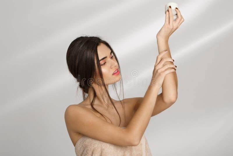 Kvinna som applicerar fuktighetsbevarande hudkräm på den vänstra handen, når att ha badat kvinna för grå frisyr för bakgrundsskön arkivbilder