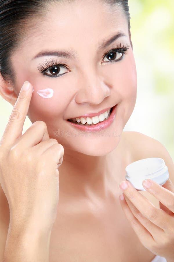 Kvinna som applicerar fuktighetsbevarande hudkrämkräm arkivbilder