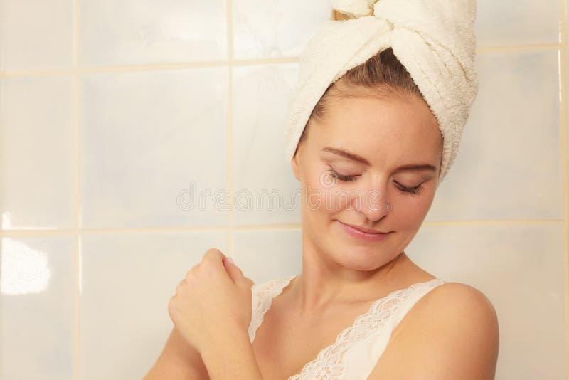 Kvinna som applicerar fuktighetsbevarande hudkr?mkr?m p? hennes kropp royaltyfri fotografi