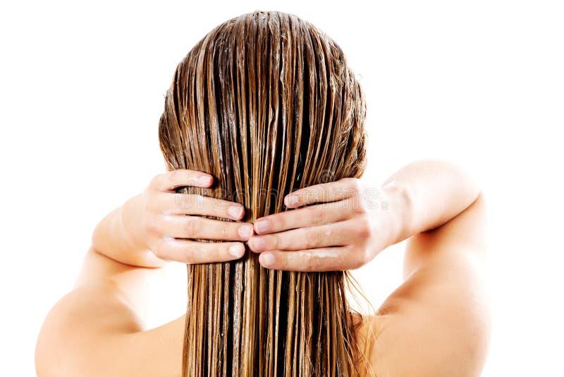 Kvinna som applicerar hårhårbalsamen Isolerat på vit royaltyfri foto