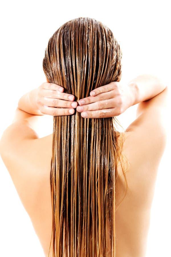 Kvinna som applicerar hårhårbalsamen Isolerat på vit arkivfoto
