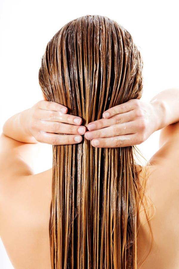 Kvinna som applicerar hårhårbalsamen Isolerat på vit royaltyfri fotografi