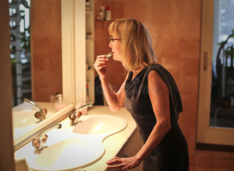 Kvinna som applicerar läppstift royaltyfria bilder