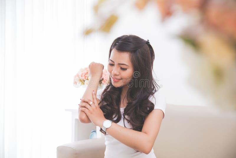 Kvinna som applicerar lotion in i hennes hud arkivbild