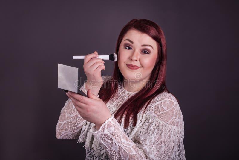 Kvinna som applicerar makeup med spegeln för borsteinnehavöverenskommelse arkivfoton