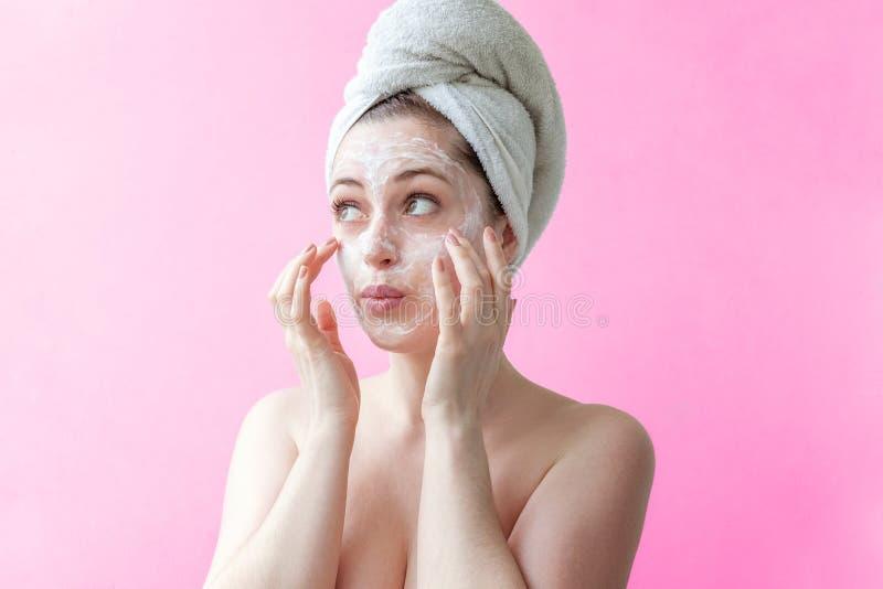 Kvinna som applicerar maskeringen eller kräm på framsida fotografering för bildbyråer