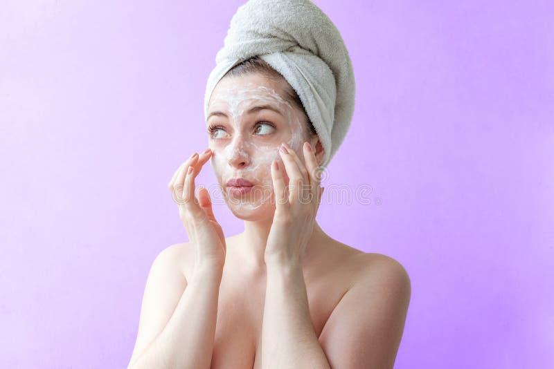 Kvinna som applicerar maskeringen eller kräm på framsida royaltyfri foto