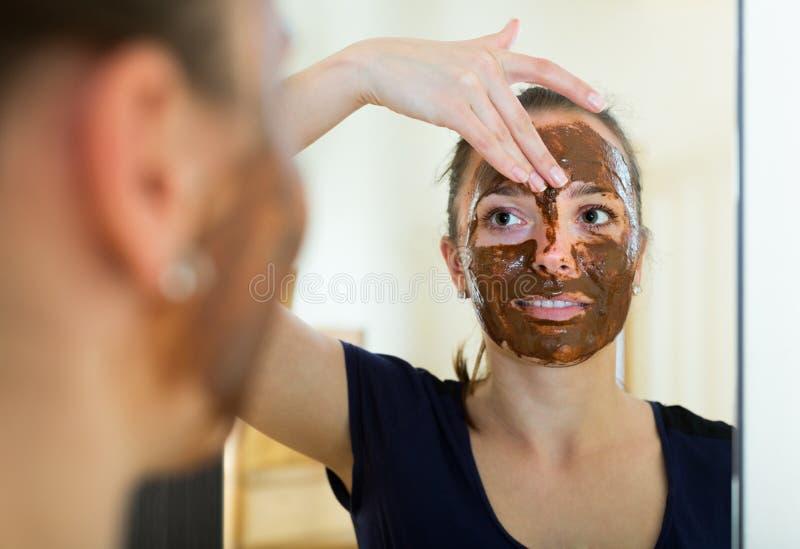 Kvinna som applicerar maskeringen på hennes framsida royaltyfri foto