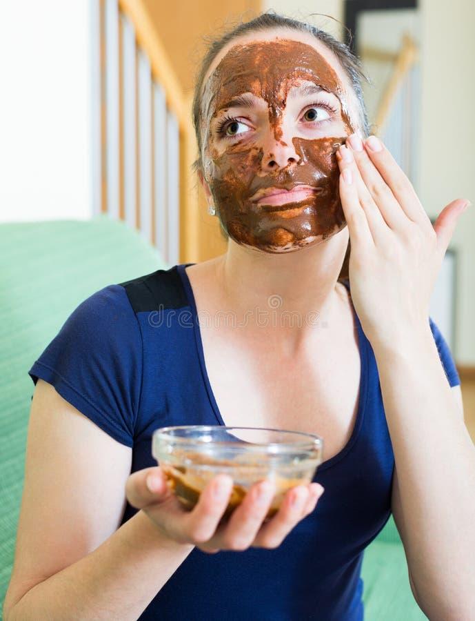 Kvinna som applicerar maskeringen på hennes framsida royaltyfri bild