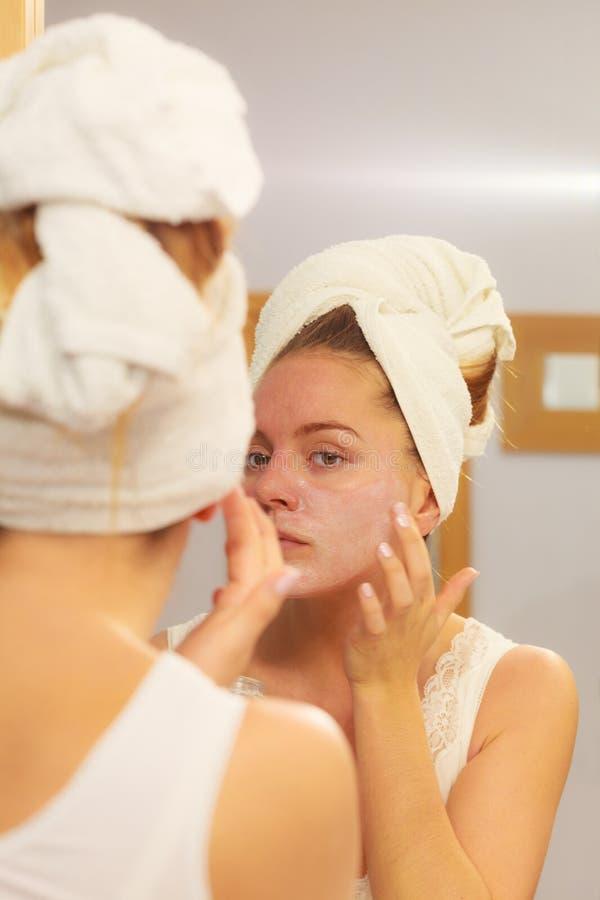 Kvinna som applicerar maskeringskräm på framsida i badrum royaltyfria foton