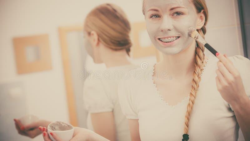 Kvinna som applicerar med maskeringen f?r borsteleragyttja till hennes framsida fotografering för bildbyråer