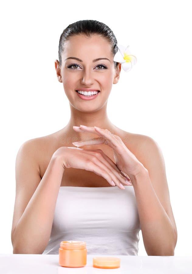Kvinna som applicerar skönhetsmedelkräm royaltyfri bild