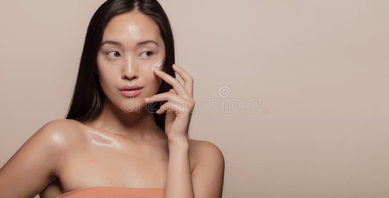 Kvinna som applicerar skönhetsprodukten på framsida arkivbilder