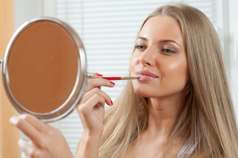 Kvinna som applicerar smink royaltyfri fotografi