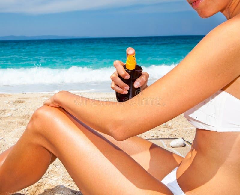 Kvinna som applicerar solkräm från en sprejflaska royaltyfri foto