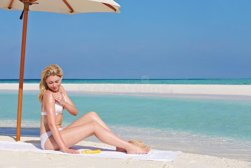 Kvinna som applicerar Sun Lotion på strandferie arkivbild