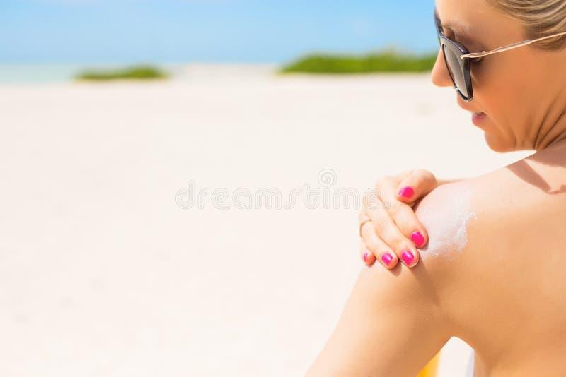Kvinna som applicerar sunscreen på stranden på varm sommardag royaltyfria bilder
