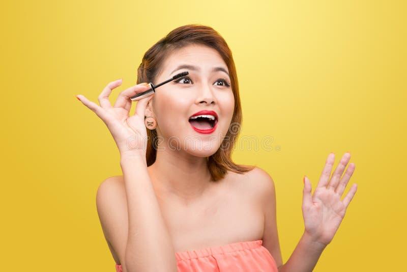 Kvinna som applicerar svart mascara på ögonfrans med makeupborsten över arkivbilder