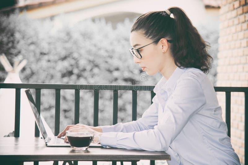 Kvinna som arbetar den hemmastadda kontorshanden på bärbara datorn royaltyfria foton