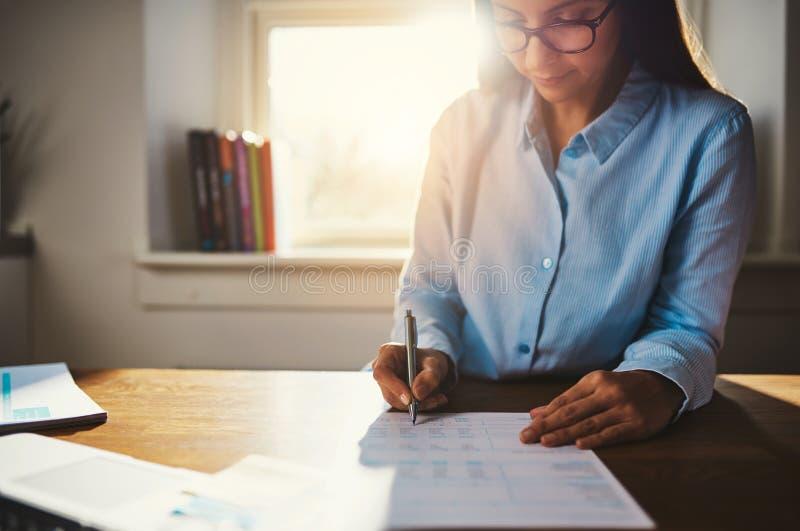 Kvinna som arbetar det hemmastadda kontoret arkivfoton