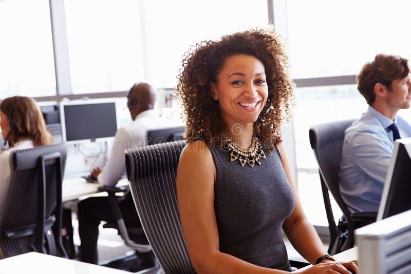 Kvinna som arbetar i en call center som ser till kameran arkivbilder