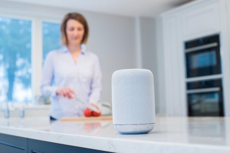 Kvinna som arbetar i kök med den smarta högtalaren i förgrund arkivfoto