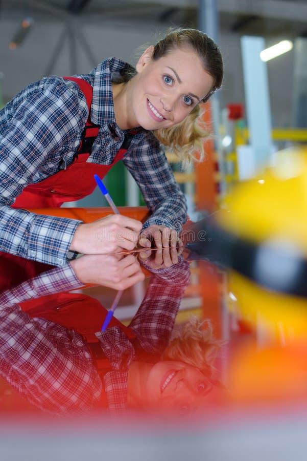 Kvinna som arbetar med arkmetall arkivbild
