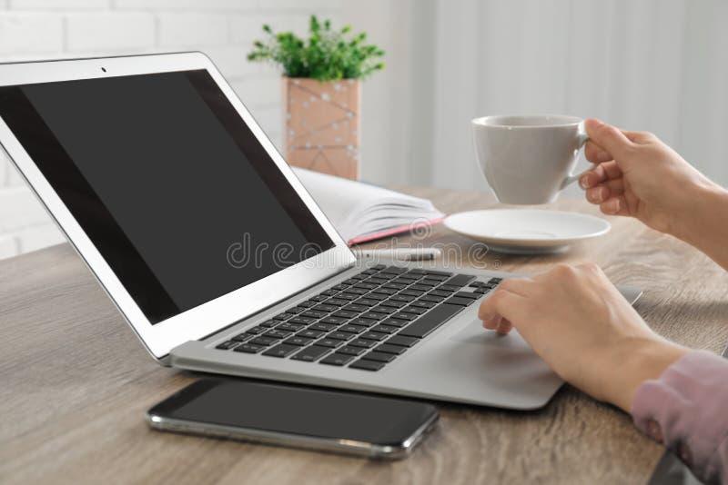 Kvinna som arbetar med b?rbara datorn p? tabellen, closeup royaltyfri foto