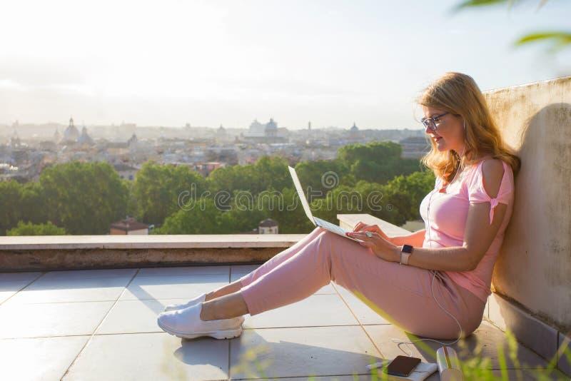 Kvinna som arbetar med bärbara datorn på terrassen som förbiser staden arkivbild