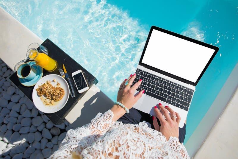 Kvinna som arbetar med bärbara datorn vid det utomhus- badkaret fotografering för bildbyråer