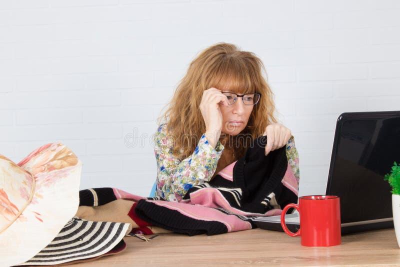 Kvinna som arbetar med kläder arkivfoton