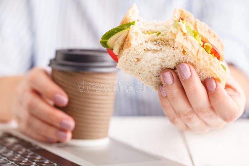 Kvinna som arbetar och äter på kontorsskrivbordet arkivbilder