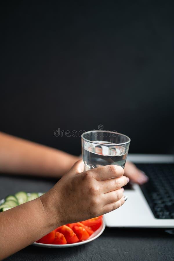 Kvinna som arbetar på bärbar datordricksvatten från exponeringsglas arkivbild
