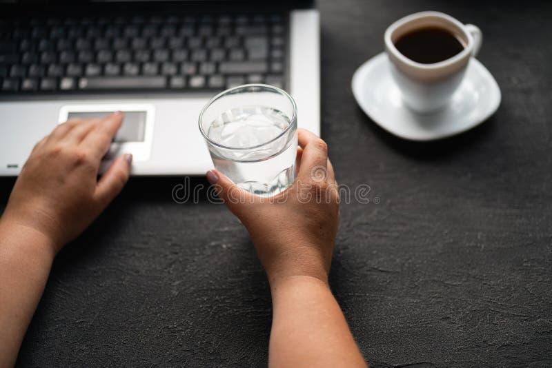 Kvinna som arbetar på bärbar datordricksvatten från exponeringsglas royaltyfri fotografi