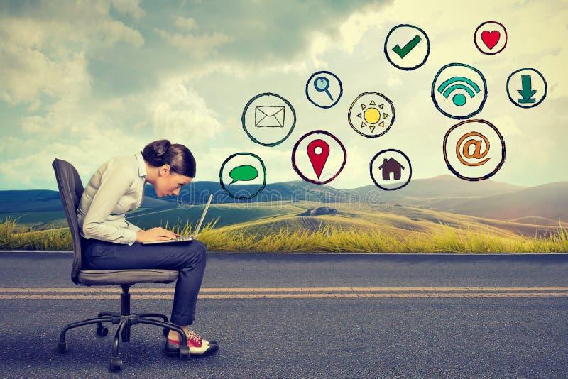 Kvinna som arbetar på bärbara datorn genom att använda social massmediaapplikation arkivbilder