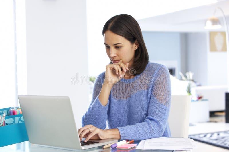 Kvinna som arbetar på bärbara datorn i inrikesdepartementet fotografering för bildbyråer