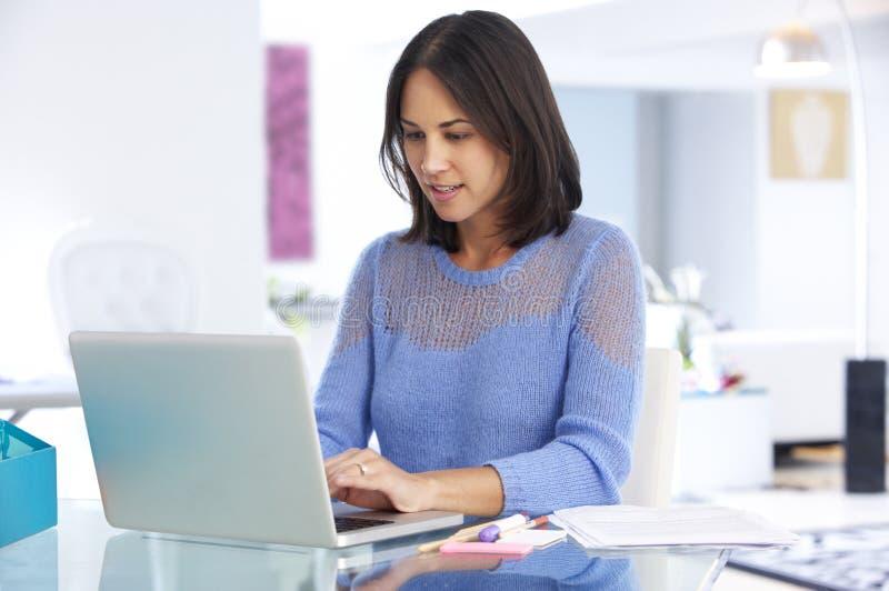 Kvinna som arbetar på bärbara datorn i inrikesdepartementet royaltyfri fotografi
