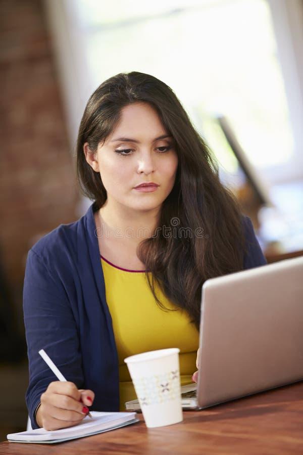 Kvinna som arbetar på bärbara datorn i modernt kontor fotografering för bildbyråer