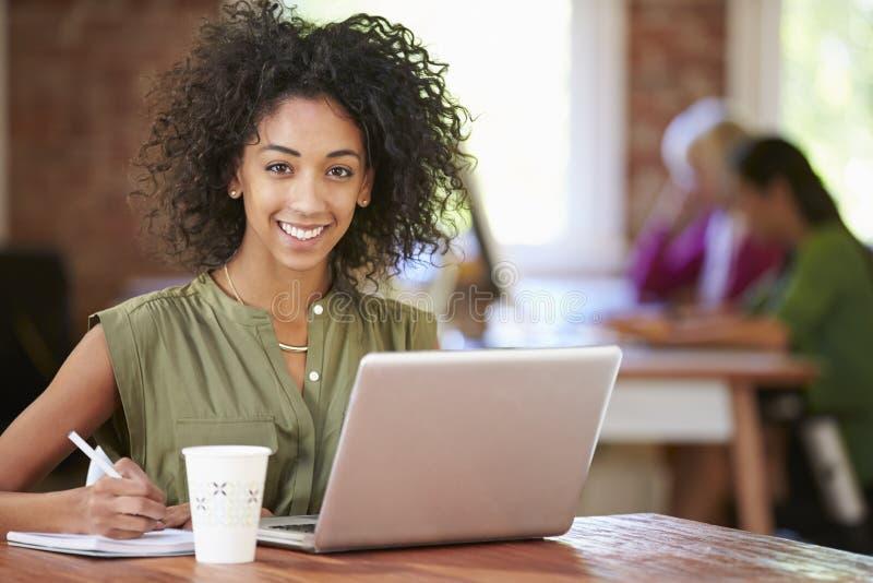 Kvinna som arbetar på bärbara datorn i modernt kontor arkivfoton