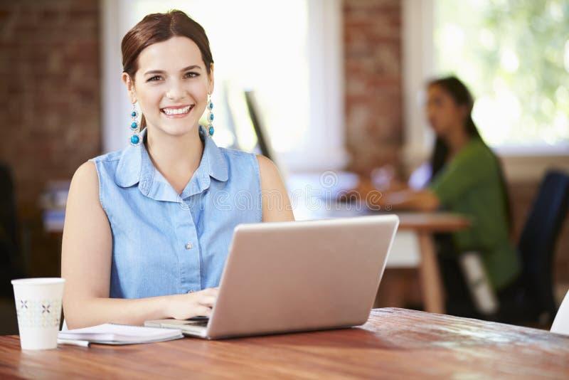 Kvinna som arbetar på bärbara datorn i modernt kontor royaltyfri foto