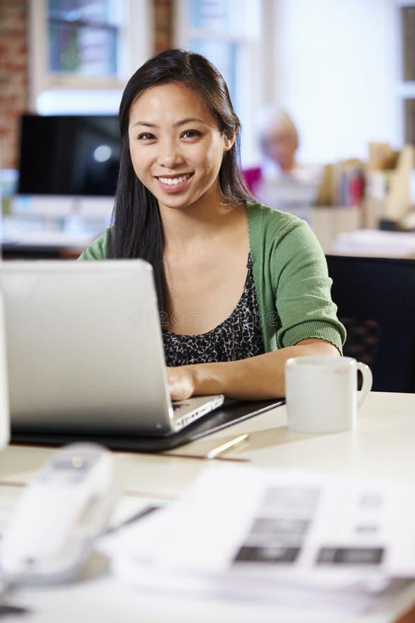 Kvinna som arbetar på bärbara datorn i modernt kontor royaltyfria foton