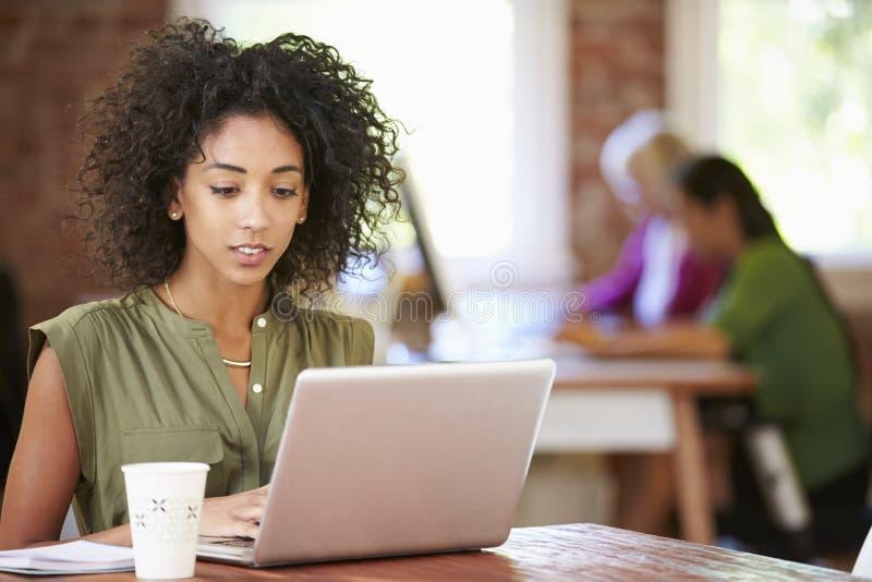 Kvinna som arbetar på bärbara datorn i modernt kontor arkivbilder