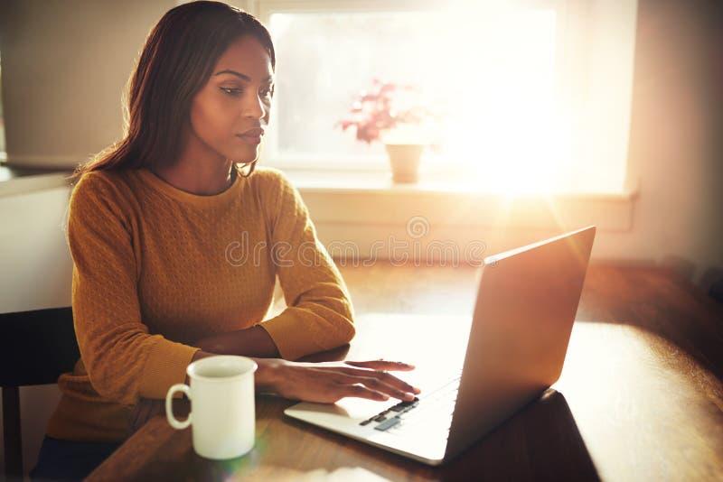 Kvinna som arbetar på bärbara datorn med ljust solljus arkivfoton