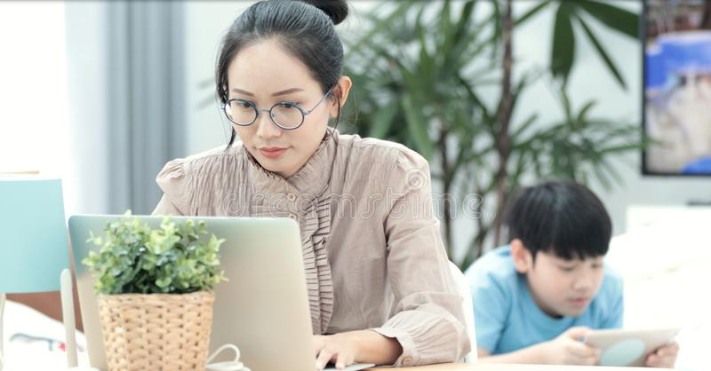 Kvinna som arbetar på bärbara datorn med pojken som spelar minnestavladatoren royaltyfri fotografi
